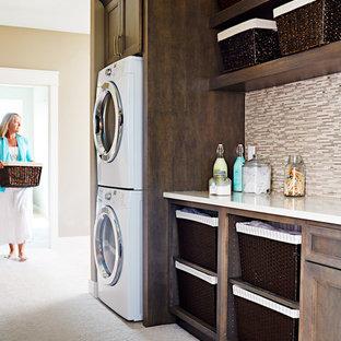 Immagine di una lavanderia multiuso design di medie dimensioni con lavello sottopiano, ante con bugna sagomata, ante grigie, top in quarzo composito, moquette, lavatrice e asciugatrice a colonna e pareti marroni