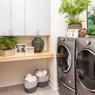 Mid-sized transitional l-shaped ceramic floor and gray floor dedicated laundry room photo in Other with shaker cabinets, gray cabinets, wood countertops and white walls