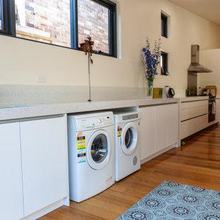 Idéer för att renovera ett mellanstort funkis grå linjärt grått grovkök, med en undermonterad diskho, släta luckor, vita skåp, bänkskiva i terrazo, grått stänkskydd, beige väggar, mellanmörkt trägolv, en tvättmaskin och torktumlare bredvid varandra och brunt golv