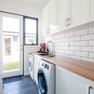 Photo of a mid-sized transitional single-wall dedicated laundry room in Melbourne with white cabinets, wood benchtops, white walls, ceramic floors, grey floor, brown benchtop, a drop-in sink, recessed-panel cabinets and a side-by-side washer and dryer.