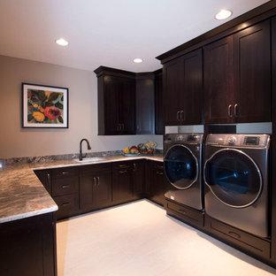 Inredning av en modern stor u-formad liten tvättstuga, med en undermonterad diskho, skåp i shakerstil, skåp i mörkt trä, granitbänkskiva, beige väggar, klinkergolv i keramik och en tvättmaskin och torktumlare bredvid varandra
