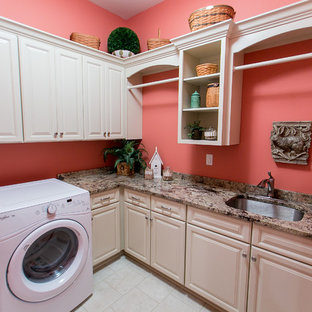 Example of a large transitional l-shaped dedicated laundry room design in Louisville with an undermount sink, raised-panel cabinets, white cabinets, granite countertops, pink walls and a side-by-side washer/dryer