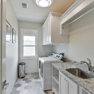 Idéer för mellanstora vintage linjära tvättstugor enbart för tvätt, med en undermonterad diskho, skåp i shakerstil, vita skåp, granitbänkskiva, vita väggar, klinkergolv i keramik och en tvättmaskin och torktumlare bredvid varandra