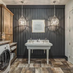 Immagine di una grande sala lavanderia tradizionale con ante con riquadro incassato, ante in legno scuro, pareti grigie, lavatrice e asciugatrice affiancate, pavimento marrone, lavatoio, top in granito, pavimento in gres porcellanato e top multicolore