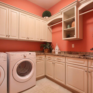 Large elegant l-shaped ceramic tile dedicated laundry room photo in Louisville with an undermount sink, raised-panel cabinets, white cabinets, granite countertops, pink walls and a side-by-side washer/dryer