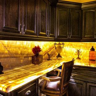 Cette image montre une petit buanderie méditerranéenne dédiée avec un placard avec porte à panneau surélevé, des portes de placard noires, un plan de travail en onyx et un plan de travail jaune.