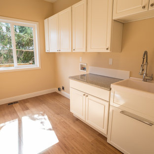 Design ideas for a mid-sized single-wall dedicated laundry room in Seattle with a drop-in sink, recessed-panel cabinets, white cabinets, terrazzo benchtops, beige walls, bamboo floors, a side-by-side washer and dryer, brown floor and multi-coloured benchtop.
