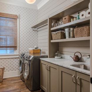 Idéer för att renovera en lantlig linjär tvättstuga enbart för tvätt, med en undermonterad diskho, bruna skåp, mörkt trägolv, en tvättmaskin och torktumlare bredvid varandra, brunt golv, skåp i shakerstil och grå väggar