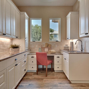 Inspiration for a large classic u-shaped utility room in Austin with a submerged sink, raised-panel cabinets, white cabinets, beige walls, granite worktops, porcelain flooring and a side by side washer and dryer.