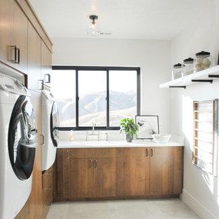 Immagine di una lavanderia design con lavello integrato, ante lisce, pareti bianche, lavatrice e asciugatrice affiancate, pavimento grigio, top bianco e ante in legno scuro