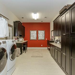 Klassisk inredning av ett mycket stort u-format grovkök, med luckor med infälld panel, svarta skåp, bänkskiva i koppar, röda väggar, laminatgolv, en tvättmaskin och torktumlare bredvid varandra och beiget golv