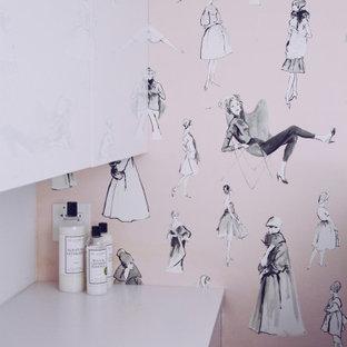 Ispirazione per una sala lavanderia minimalista di medie dimensioni con lavello sottopiano, ante lisce, ante bianche, top in quarzo composito, pareti rosa, pavimento in gres porcellanato, lavatrice e asciugatrice affiancate, pavimento grigio e top bianco