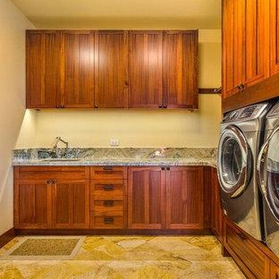 Foto di una grande sala lavanderia american style con lavello sottopiano, ante in stile shaker, ante in legno scuro, top in granito, pareti gialle e pavimento in travertino