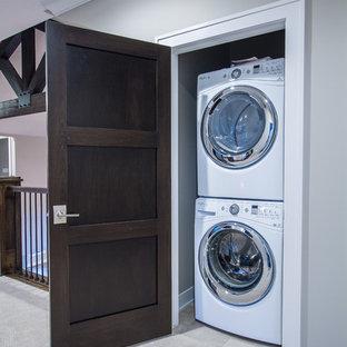 Ispirazione per un piccolo ripostiglio-lavanderia tradizionale con moquette e lavatrice e asciugatrice a colonna