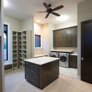 Photo of a large traditional u-shaped utility room in Omaha with shaker cabinets, dark wood cabinets, composite countertops, beige walls, carpet and a side by side washer and dryer.