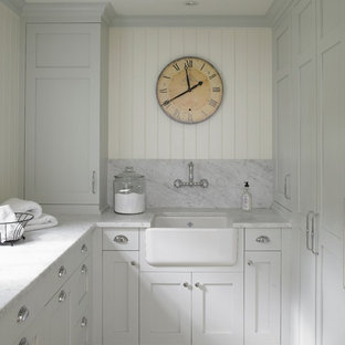 Design ideas for a traditional laundry room in New York with a farmhouse sink, limestone floors and grey benchtop.