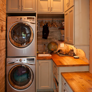 Mid-sized mountain style galley ceramic tile utility room photo in Other with a drop-in sink, shaker cabinets, gray cabinets, wood countertops, brown walls and a stacked washer/dryer