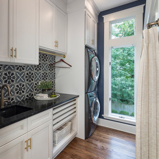 Photo of a traditional single-wall separated utility room in Cincinnati with a submerged sink, recessed-panel cabinets, white cabinets, blue walls, dark hardwood flooring, a stacked washer and dryer, brown floors and black worktops.