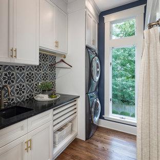 Esempio di una sala lavanderia tradizionale con lavello sottopiano, ante con riquadro incassato, ante bianche, pareti blu, parquet scuro, lavatrice e asciugatrice a colonna, pavimento marrone e top nero