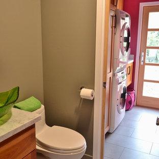 Aménagement d'une petit buanderie linéaire contemporaine multi-usage avec un évier encastré, un placard à porte shaker, des portes de placard en bois sombre, un plan de travail en granite, un mur rose, un sol en carrelage de porcelaine et des machines superposées.