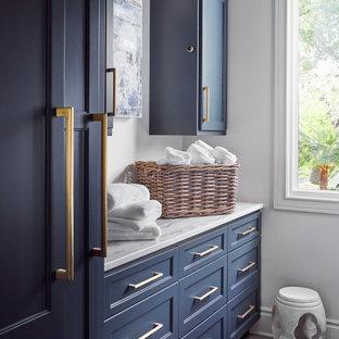 Klassisk inredning av en mellanstor vita parallell vitt tvättstuga enbart för tvätt, med luckor med infälld panel, blå skåp, bänkskiva i kvartsit, stänkskydd i sten, vita väggar, kalkstensgolv, en tvättmaskin och torktumlare bredvid varandra och grått golv