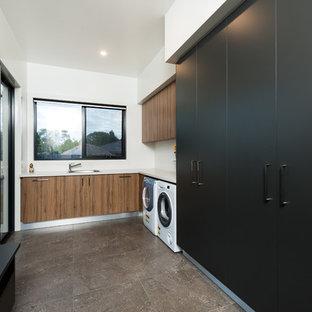 Foto di una grande lavanderia multiuso contemporanea con lavello da incasso, ante in legno scuro, top in quarzo composito, pareti bianche, pavimento in gres porcellanato e lavatrice e asciugatrice affiancate