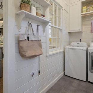 Lantlig inredning av en tvättstuga, med skåp i shakerstil, klinkergolv i porslin, en tvättmaskin och torktumlare bredvid varandra och grått golv