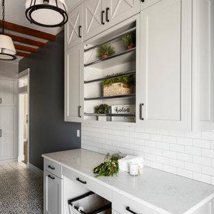 Klassisk inredning av en vita parallell vitt tvättstuga enbart för tvätt, med en nedsänkt diskho, skåp i shakerstil, grå skåp, bänkskiva i kvarts, vitt stänkskydd, stänkskydd i tunnelbanekakel, blå väggar, klinkergolv i porslin, en tvättmaskin och torktumlare bredvid varandra och flerfärgat golv