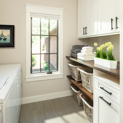 Mid-sized elegant galley porcelain tile and gray floor dedicated laundry room photo in Detroit with a drop-in sink, shaker cabinets, white cabinets, wood countertops, beige walls, a side-by-side washer/dryer and brown countertops