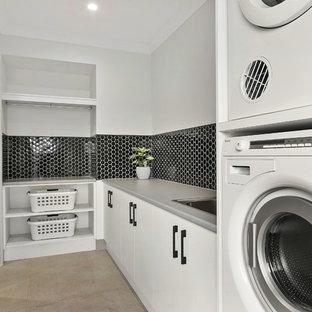 Foto på en funkis grå tvättstuga enbart för tvätt, med släta luckor, vita skåp, grå väggar, en tvättpelare och beiget golv