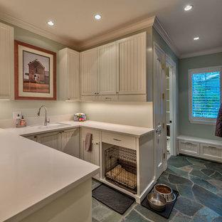 Foto di una grande lavanderia multiuso classica con lavello sottopiano, ante a filo, ante bianche, top in quarzo composito, pareti verdi, pavimento in ardesia, pavimento multicolore e top beige