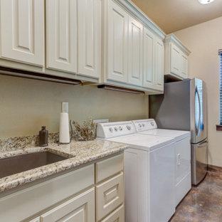 Bild på en mellanstor rustik beige parallell beige tvättstuga enbart för tvätt, med en undermonterad diskho, luckor med upphöjd panel, vita skåp, granitbänkskiva, beige stänkskydd, beige väggar, betonggolv, en tvättmaskin och torktumlare bredvid varandra och svart golv