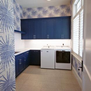 Idee per una grande lavanderia multiuso tropicale con lavello sottopiano, ante con riquadro incassato, ante blu, top in quarzite, pareti multicolore, pavimento con piastrelle in ceramica, lavatrice e asciugatrice affiancate, pavimento grigio e top bianco