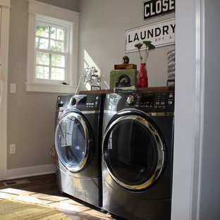 Laundry room - transitional single-wall dark wood floor and brown floor laundry room idea in Other with wood countertops, gray walls, a side-by-side washer/dryer and brown countertops