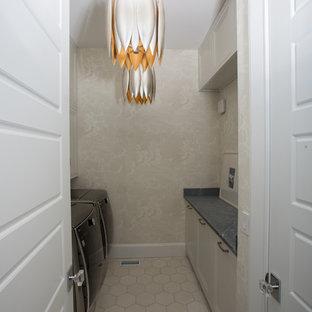 Cette image montre une petite buanderie parallèle minimaliste dédiée avec un placard avec porte à panneau encastré, des portes de placard blanches, un plan de travail en stéatite, béton au sol, des machines côte à côte et un sol blanc.