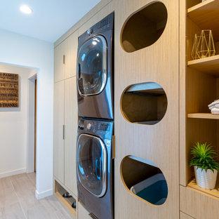 Idée de décoration pour une buanderie linéaire design multi-usage et de taille moyenne avec un placard à porte plane, des portes de placard en bois clair, un mur blanc, un sol en bois clair, des machines superposées et un sol beige.