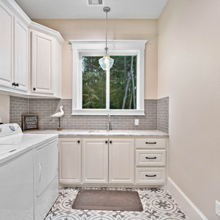 Dedicated laundry room - french country l-shaped gray floor dedicated laundry room idea in Houston with an undermount sink, raised-panel cabinets, beige cabinets, beige walls, a side-by-side washer/dryer and beige countertops