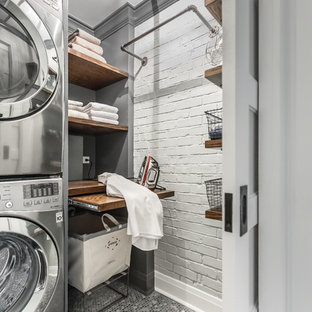 Laundry room - small industrial porcelain floor laundry room idea in Chicago with wood countertops, gray walls, a stacked washer/dryer, open cabinets and brown countertops