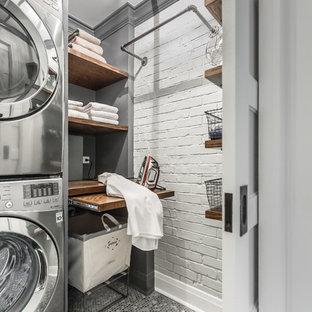 Imagen de lavadero industrial, pequeño, con encimera de madera, paredes grises, suelo de baldosas de porcelana, lavadora y secadora apiladas, armarios abiertos y encimeras marrones
