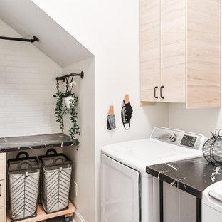 Idéer för mellanstora industriella l-formade svart tvättstugor enbart för tvätt, med släta luckor, skåp i ljust trä, laminatbänkskiva, vita väggar, linoleumgolv, en tvättmaskin och torktumlare bredvid varandra och flerfärgat golv