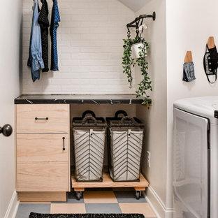 Idéer för att renovera en mellanstor industriell svarta l-formad svart tvättstuga enbart för tvätt, med släta luckor, skåp i ljust trä, laminatbänkskiva, vita väggar, linoleumgolv, en tvättmaskin och torktumlare bredvid varandra och flerfärgat golv