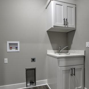 Esempio di una sala lavanderia industriale con lavello a doppia vasca, ante in stile shaker, ante bianche, top in quarzo composito e lavatrice e asciugatrice affiancate