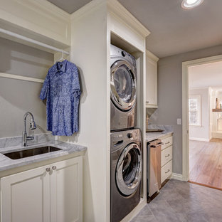 Large traditional galley utility room in Oklahoma City with a submerged sink, shaker cabinets, white cabinets, grey walls, ceramic flooring, a stacked washer and dryer, marble worktops, grey floors and grey worktops.