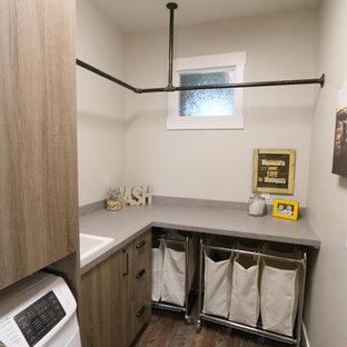 Idéer för att renovera en industriell l-formad tvättstuga, med släta luckor, laminatbänkskiva, en tvättmaskin och torktumlare bredvid varandra och skåp i mellenmörkt trä