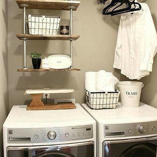 Idéer för en liten industriell liten tvättstuga, med beige väggar och en tvättmaskin och torktumlare bredvid varandra