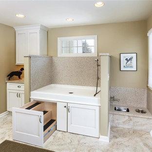 Foto di una grande lavanderia design con ante bianche, top in superficie solida, pareti beige, pavimento con piastrelle in ceramica, lavatrice e asciugatrice affiancate e ante in stile shaker
