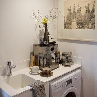 Esempio di una piccola lavanderia multiuso minimal con lavello a vasca singola, ante bianche, top in superficie solida, pareti bianche e parquet scuro