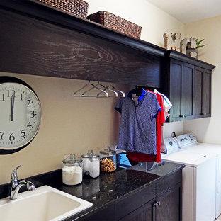 タンパの大きいモダンスタイルのおしゃれな洗濯室 (ドロップインシンク、落し込みパネル扉のキャビネット、濃色木目調キャビネット、オニキスカウンター、ベージュの壁、磁器タイルの床、左右配置の洗濯機・乾燥機) の写真
