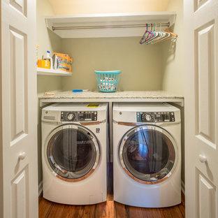 Exempel på en liten klassisk flerfärgade linjär flerfärgat liten tvättstuga, med bänkskiva i kvarts, beige väggar, mellanmörkt trägolv, en tvättmaskin och torktumlare bredvid varandra och brunt golv