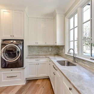 Photo of a large traditional l-shaped separated utility room in Charlotte with a submerged sink, shaker cabinets, white cabinets, quartz worktops, white walls, medium hardwood flooring and a side by side washer and dryer.